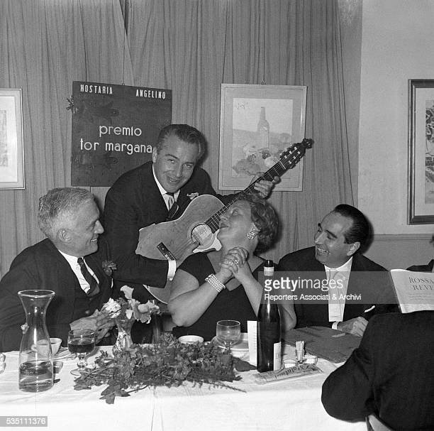 Italian actor Rossano Brazzi singing a serenade to his wife Lidia Bertolini during a dinner for the Tor Margana award ceremony at the Hosteria...
