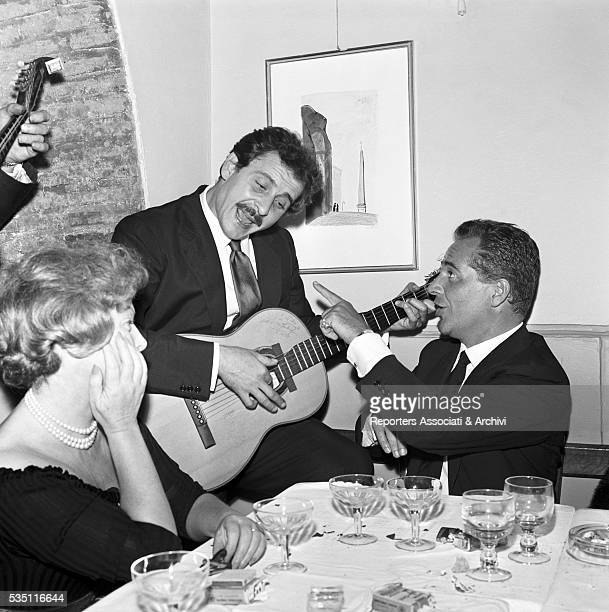 Italian actor Rossano Brazzi singing accompanied by Italian singersongwriter Domenico Modugno at the guitar during a dinner at the restaurant...