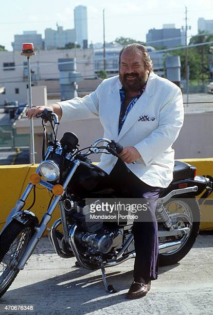 Italian actor scriptwriter and film producer Bud Spencer smiling on a motorcycle on the set of the film Extralarge Miami Killer 1991