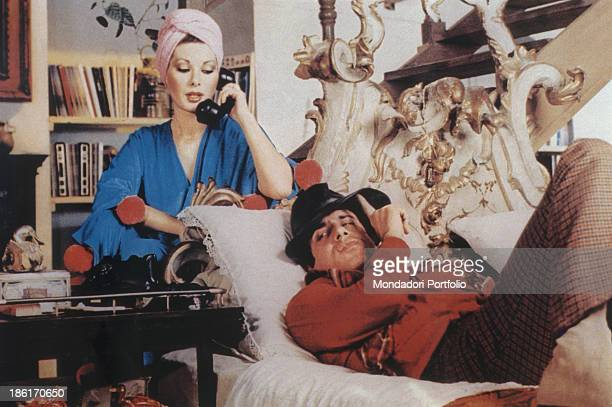 Italian actor singer and songwriter Adriano Celentano lying on a sofa while Frenchborn Italian actress Edwige Fenech is speaking over the phone in...
