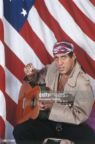 Italian actor singer and songwriter Adriano Celentano playing guitar in front of the American flag 1984