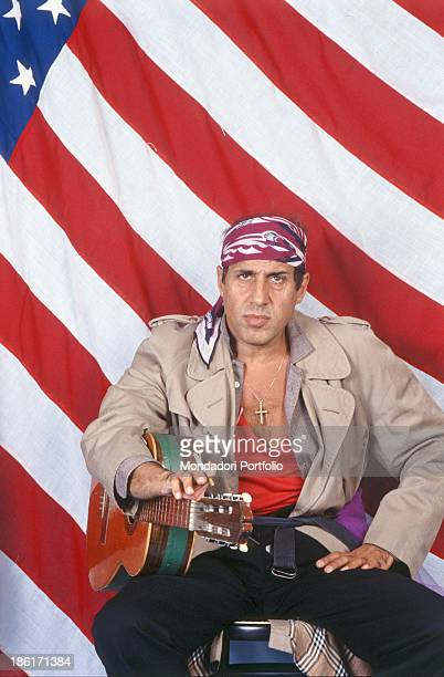 Italian actor singer and songwriter Adriano Celentano sitting in front of the American flag with a cigarette in the hand and the guitar under his arm...