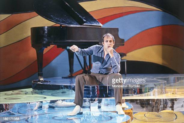 Italian actor singer and songwriter Adriano Celentano speaking seated on a stage 1979