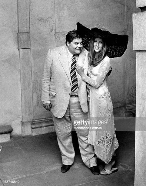 Italian actor Tino Buazzelli grimacing to Italian actress Stefania Sandrelli wearing a big lace hat and posing on the film set of Devil in the Brain...