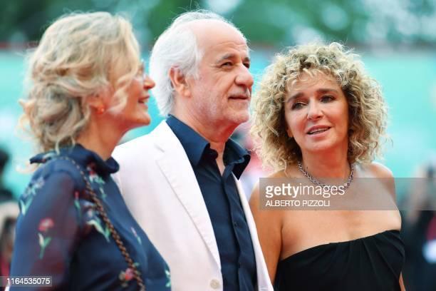 Italian actor Toni Servillo , his wife Italian actress Manuela Lamanna and Italian actress Valeria Golino pose as they arrive for the opening...