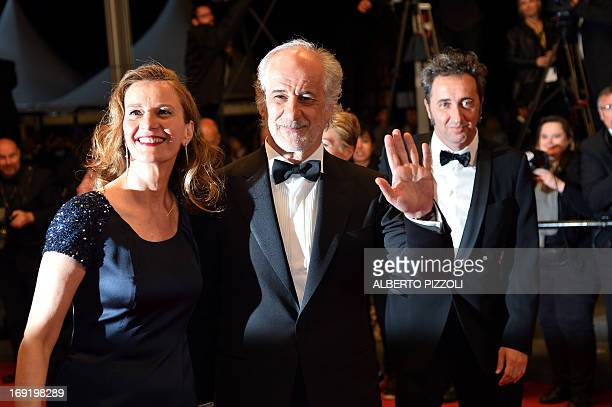 """Italian actor Toni Servillo waves on May 21, 2013 as he arrives with his wife actress Manuela Lamanna for the screening of the film """"La Grande..."""
