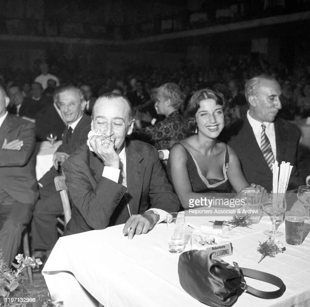 Italian actor Totò and his partner and Italian actress Franca Faldini smiling while sitting at the table during the Maschere d'Argento awarding...