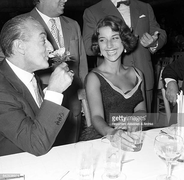 Italian actor Totò and his wife Italian actress Franca Faldini, sitting at a dinner table during a party. Rome, 1955