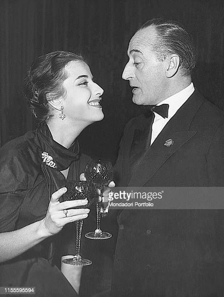 Italian actor Totò and Italian actress and his partner Franca Faldini looking into each other's eyes during a reception. Italy, 1950s