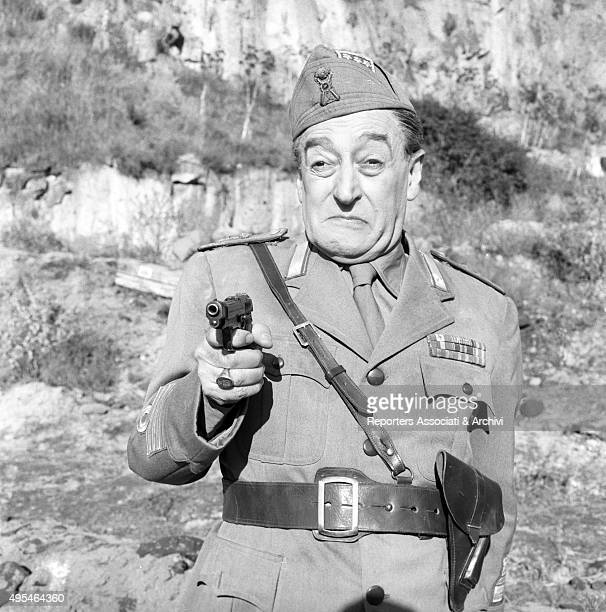 Italian actor Totò holding a gun in the film The Two Colonels 1962