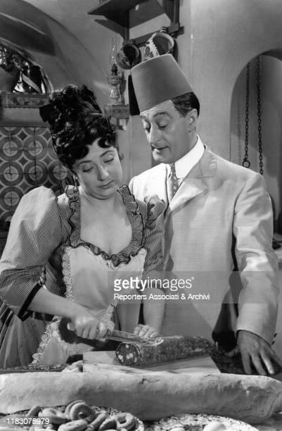 Italian actor Totò looking at Italian actress Anna Campori slicing a salami in the film Neapolitan Turk 1953