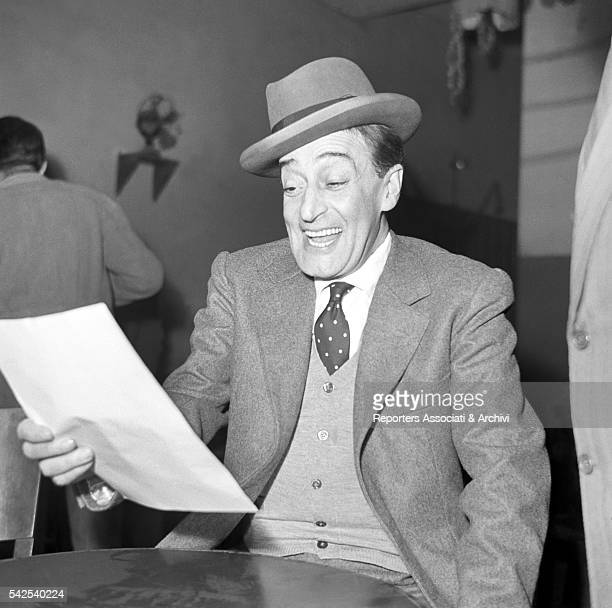 Italian actor Totò smiling and reading a sheet Rome 1949