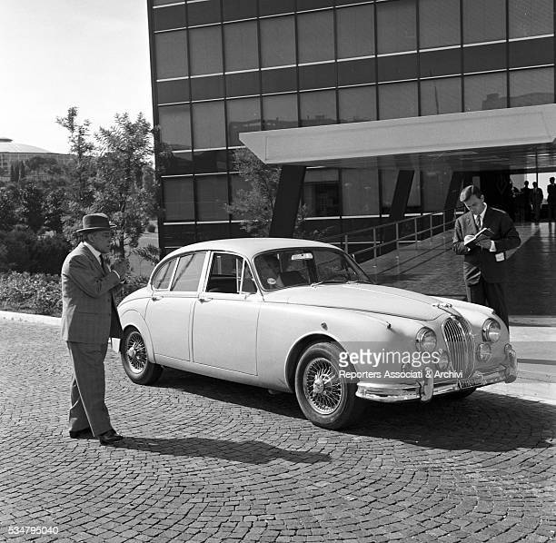 Italian actor Totò walking next to a Jaguar in The Commandant Italy 1963