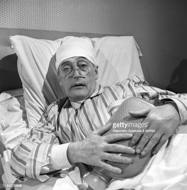 Italian actor Totò with the hot water bottle in the film Totò Peppino and the Hussy 1956