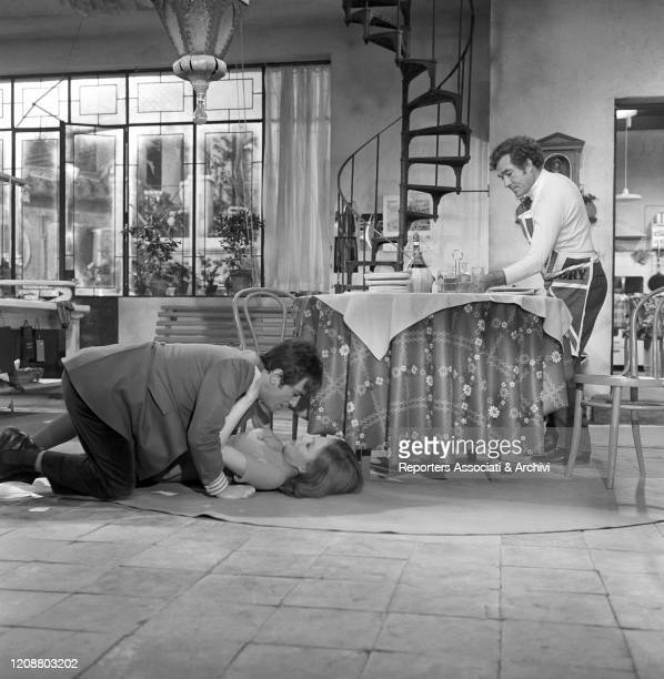 Italian actor Ugo Tognazzi setting the table while Italian actor Nino Manfredi and American actress Pamela Tiffin are hugging each other on the floor...