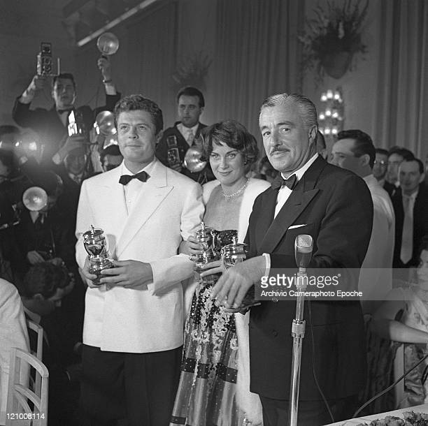 Italian actor Vittorio De Sica wearing a tuxedo and a bow tie portraiyed with Alida Valli and Marcello Mastroianni during the St Vincent prizegiving...