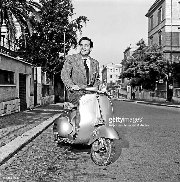 Italian actor Vittorio Gassman posing on a Vespa in the streets of Rome Rome 1957