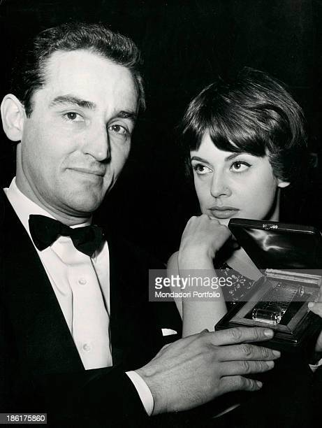 Italian actor Vittorio Gassman showing an award that he just won Italian actress Anna Maria Ferrero looking at him 1968