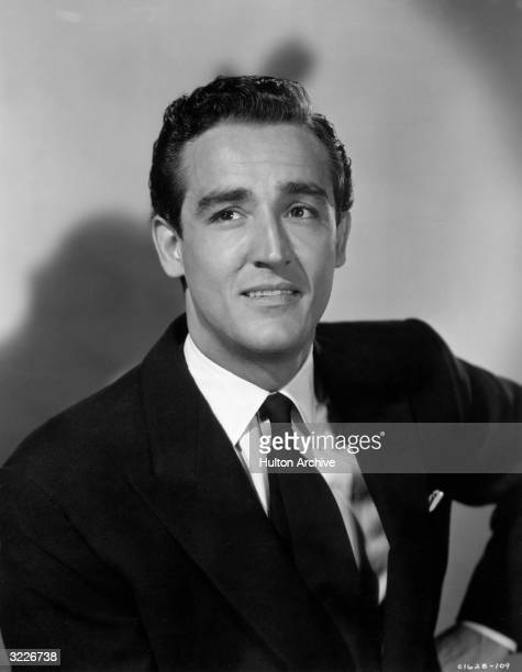 Italian actor Vittorio Gassman smiles and holds his hand to his hip while wearing a jacket and a tie in a promotional portrait for director Charles...