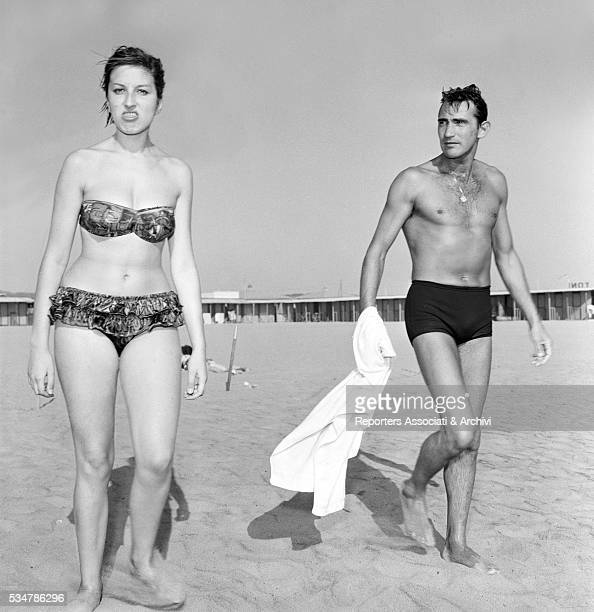 Italian actor Walter Chiari and Italian singer Mina in swimsuit at Fregene's beach Fregene 1960