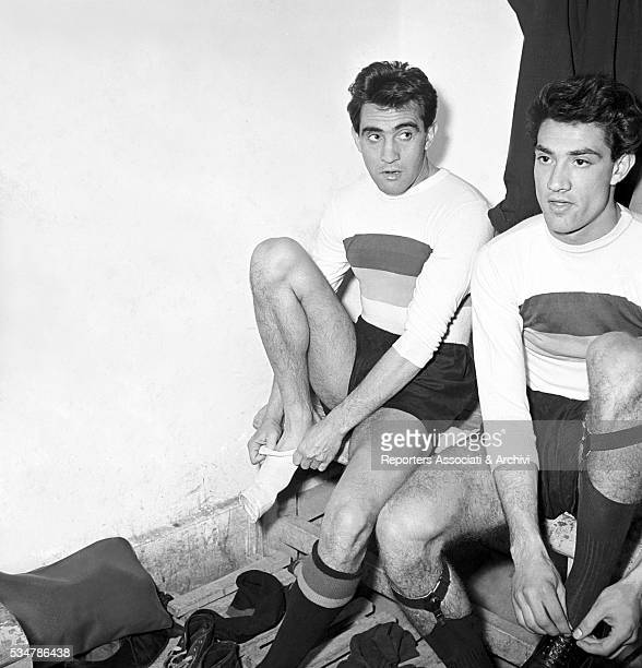 Italian actor Walter Chiari putting on a sock in the dressing room for a football match with the Actors' Team 1951
