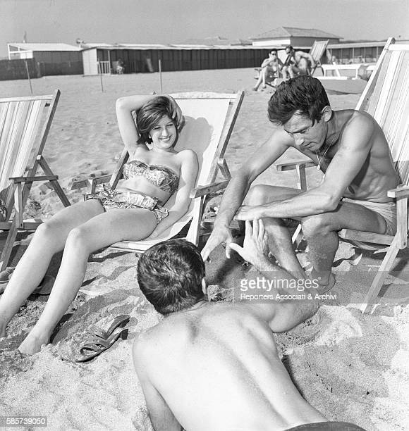 Italian actor Walter Chiari sitting on the beach chair in swimsuit at the sea with the singer Mina Mazzini and another friend Fregene Fiumicino 1960