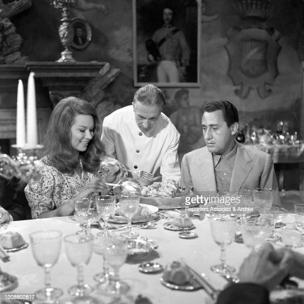 Italian actors Alberto Sordi and Lea Massari sitting at the table in the film A Difficult Life. Italy, 1961