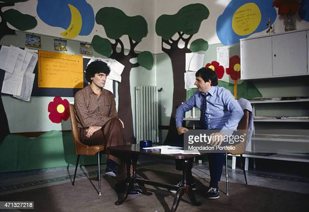 Italian actors and directors Massimo Troisi and Marco Messeri sitting in a classroom in the film I'm Starting from Three 1981