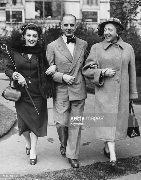 Italian actors Andreina Pagnani Sergio Tofano and Margherita Bagni walking arm in arm through London following an invite from Sir Laurence Olivier...