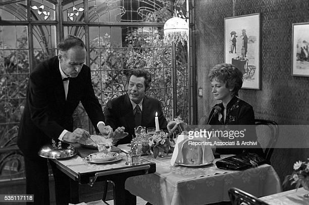 Italian actors Carla Gravina and Marcello Mastroianni sitting at the table in the film The Terrace 1980