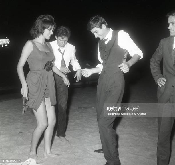 Italian actors Franco Interlenghi Antonella Lualdi and French actor Laurent Terzieff dancing on the sand under Italian director and writer Pier Paolo...