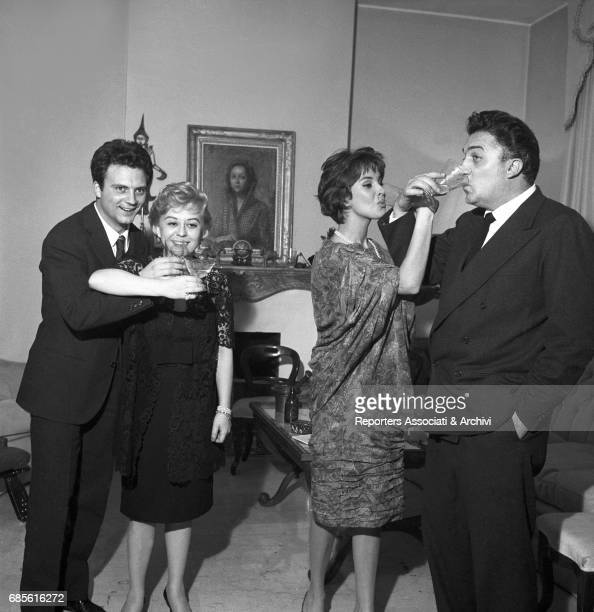Italian actors Franco Interlenghi Giulietta Masina and Antonella Lualdi and Italian director Federico Fellini having a toast for New Year's Eve at...