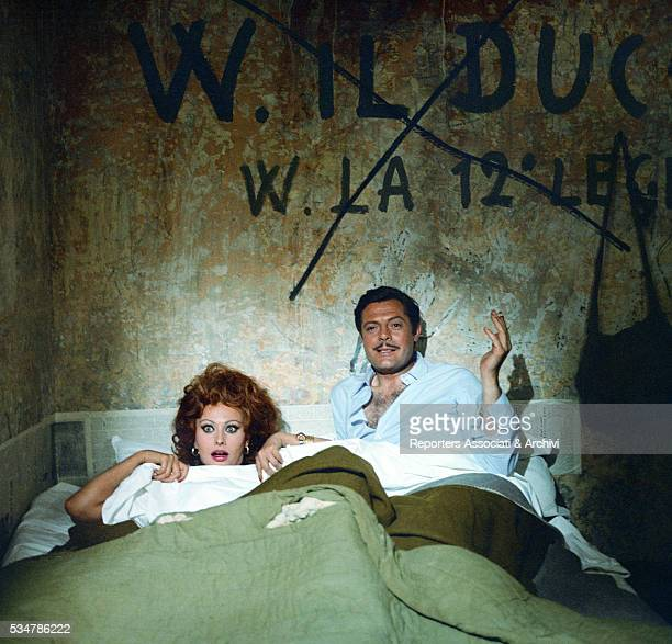 Italian actors Marcello Mastroianni and Sophia Loren lying in bed in the film Marriage Italian Style 1964