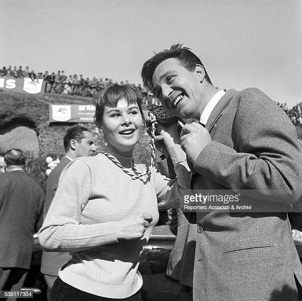 Italian actors Marisa Allasio and Franco Fabrizi smiling while listening a ticking watch at the Cinema Rally 1956