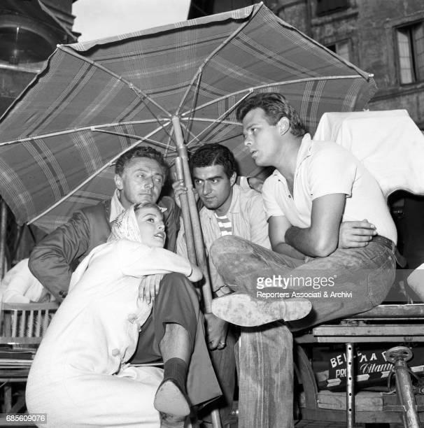 Italian actors Renato Salvatori and Alessandra Panaro with Italian director Dino Risi under a beach umbrella on the set of Pretty But Poor 1957