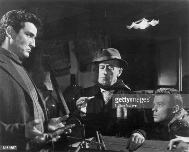Italian actors Vittorio Gassman Toto and Renato Salvatori consider a heavy object in a scene from Mario Monicelli's crime comedy 'I Soliti Ignoti'...