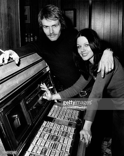 Italian actress Agostina Belli and her partner and Norwegian actor Fred Robsahm posing leaning on a juke box in the bar of the actress' sister Milan...