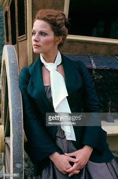 Italian actress Agostina Belli leaning on the back of a coach and wearing a stage costume 1975