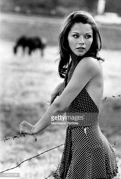 Italian actress Agostina Belli leaning on the barbed wire holding a cigarette Rome 1972