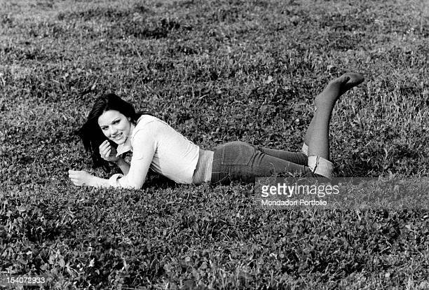 Italian actress Agostina Belli lying on the grass and chewing a blade of grass Rome 1973