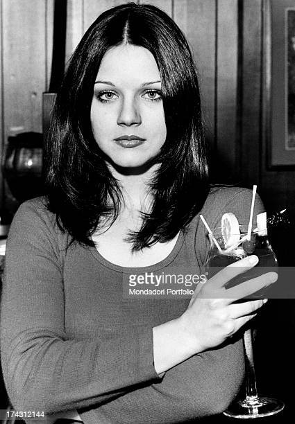 Italian actress Agostina Belli posing holding a cocktail in the bar of her sister Armida Magnoni Milan 1973
