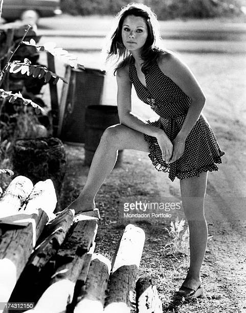 Italian actress Agostina Belli posing keeping her leg on some wooden trunks Rome 1972