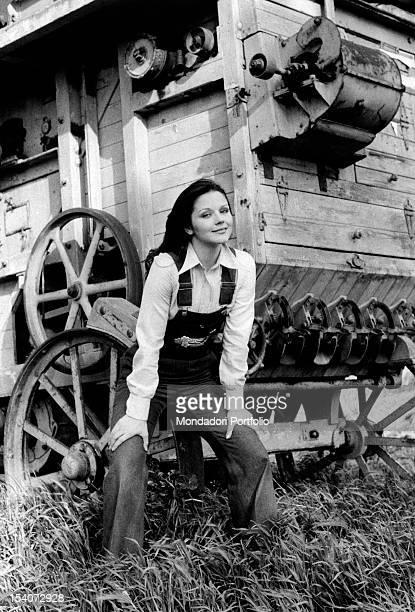 Italian actress Agostina Belli sitting on a thresher Rome 1973