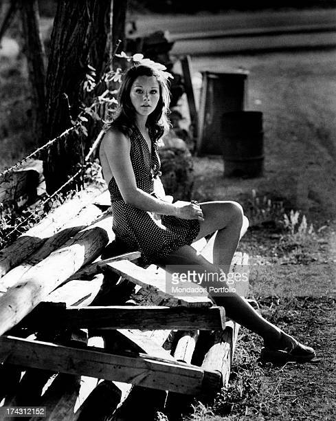 Italian actress Agostina Belli sitting on some wooden boards Rome 1972