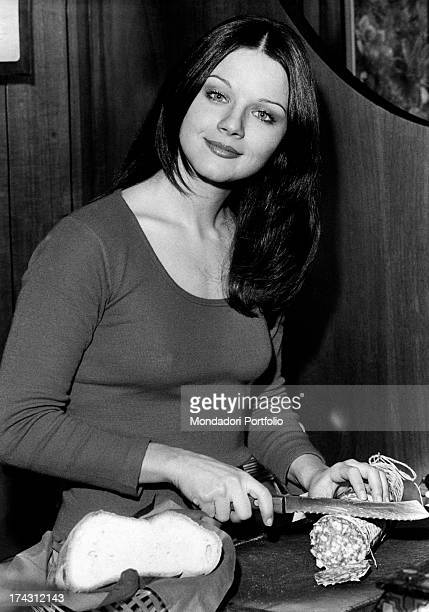 Italian actress Agostina Belli slicing salami in the bar of her sister Armida Magnoni Milan 1973