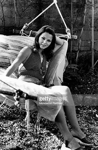 Italian actress Agostina Belli smiling and posing sitting on a hammock Rome 1972