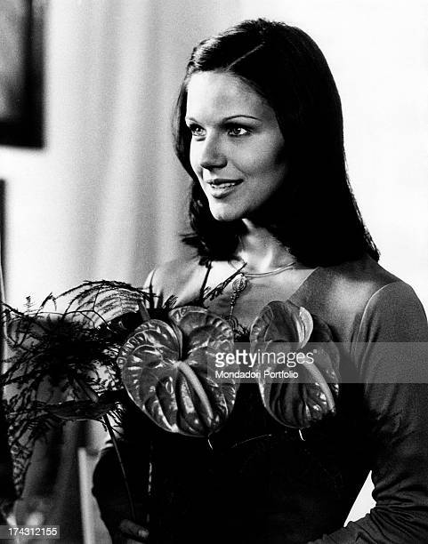 Italian actress Agostina Belli smiling holding a plant in The Governess Rome 1974