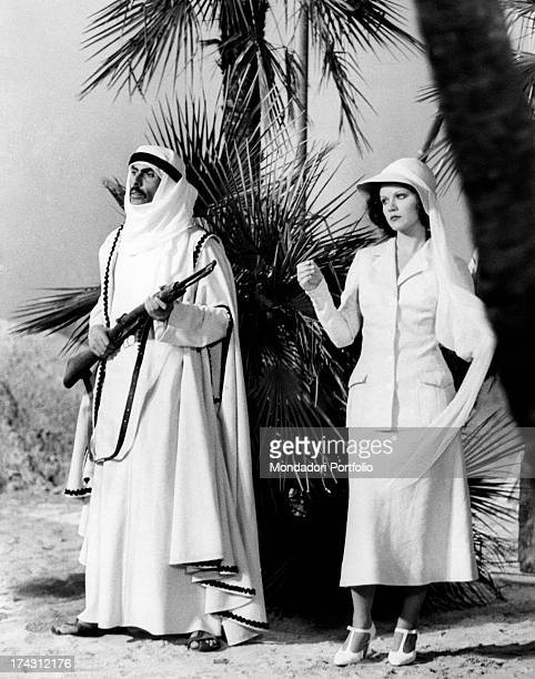 Italian actress Agostina Belli standing beside a man holding a rifle in The Career of a Chambermaid Rome 1976