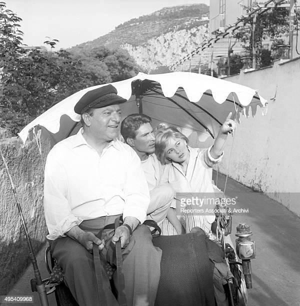 Italian actress Alessandra Panaro and Italian actor Renato Speziali looking far sitting on a coach in the film Avventura a Capri Capri 1958