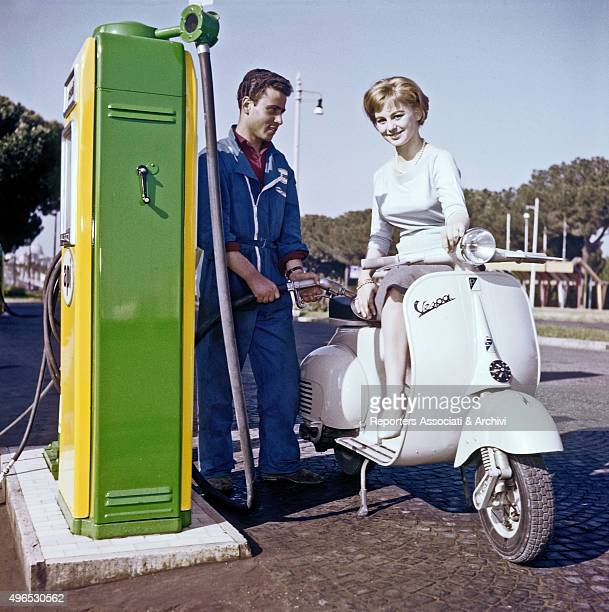 Italian actress Alessandra Panaro refueling her Vespa at a gas station on the road Rome 1957
